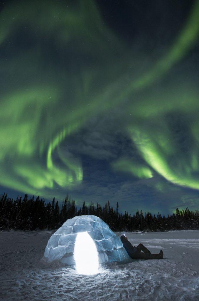 The northern lights over an igloo.