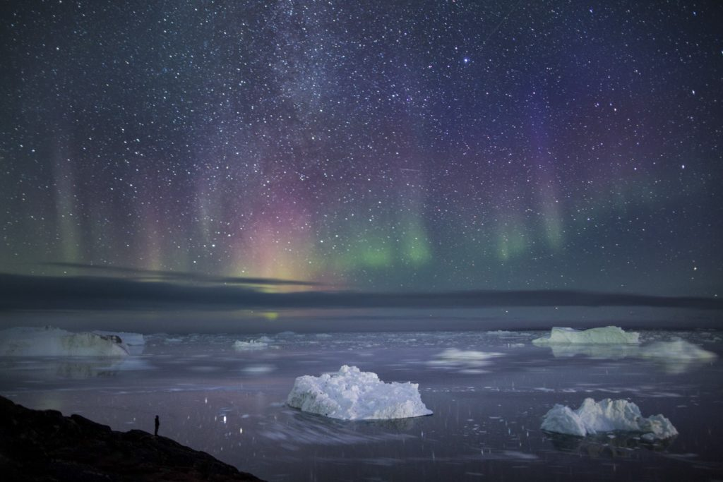 The northern lights over water and icebergs.