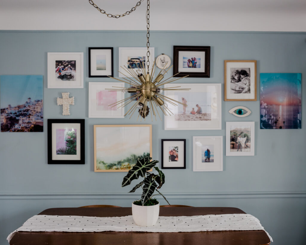 A mixed media gallery wall in a dining room.